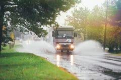 Lastwagen auf nasser Straße reitet durch eine Pfütze Lizenzfreies Stockfoto
