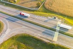 Lastwagen, die Fracht entlang Hauptstraße im ländlichen Gebiet transportieren aerial lizenzfreie stockfotos