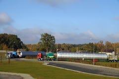 Lastzug, der aus zwei LKWs mit einer extrem langen Last besteht Überformatlast oder convoi exceptionnel stockbilder