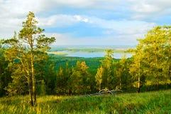Lasu krajobraz z mieszanymi lasowymi drzewami na halnych skłonach i odległy jezioro pod miękkim zmierzchem zaświecamy obraz royalty free