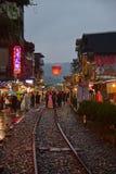 Laszowanie lampion w niebo podczas gdy trzymający umbreall na deszczowym dniu przy Shifen Starymi ulicami w opóźnionym wieczór zdjęcie royalty free