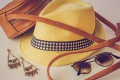 Lat akcesoria, torba, słomiany kapelusz, okulary przeciwsłoneczni i kolczyki, kłamają na stole Cztery akcesoria beżowy kolor fotografia royalty free
