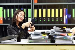 Lat asiatisk kontorskvinna som använder den smarta telefonen för mobil i arbetstid arkivfoton