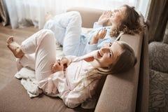 Lat-ben som gör ingenting och tillsammans tycker om fritid Övre-vinkeln sköt av gulliga kvinnor som sitter i soffa i nightwear arkivfoton