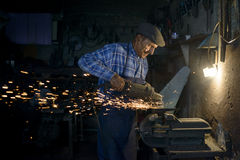 90 lat blacksmith szlifierska cioska w jego warsztacie Zdjęcia Royalty Free