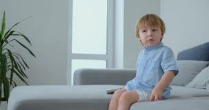 2 lat chłopiec siedzi na kanapie i ogląda TV obsiadanie z pilotem do tv w jego rękach zbiory