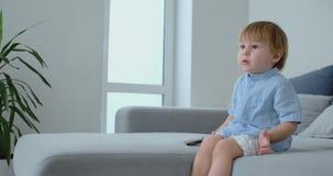 2 lat chłopiec siedzi na kanapie i ogląda TV podczas gdy siedzący z pilotem do tv w jego rękę Widok kreskówki i TV zdjęcie wideo