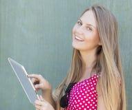 20 lat dziewczyna dotyka pastylki ono uśmiecha się i komputer Zdjęcia Royalty Free
