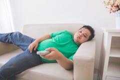 Lat fet sjukligt fet man som lägger på soffan och den hållande ögonen på tv:n fotografering för bildbyråer