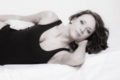 Lat kvinna för sexig flicka med kudden på säng i sovrum Arkivbilder