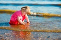 2-3 lat mała dziewczynka bawić się z otoczakami przy riverbank obraz stock