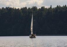Lat man och yacht Arkivfoto