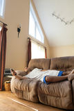 Lat man som lägger på soffan royaltyfria bilder