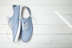 Lat przypadkowi sneakers na białym drewnianym tle Odbitkowa przestrze? dla teksta zdjęcie royalty free