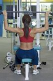 Lat Pulldown. A female fitness instructor demonstrates a lat pulldown Royalty Free Stock Images
