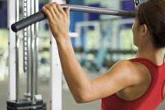 Lat Pulldown 3. A woman demonstrates a lat pulldown exercise in a gym Stock Image