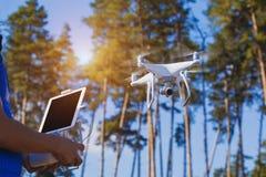 Latać copter w lasowym pilot do tv w man& x27; s ręki Zdjęcia Stock
