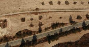Latać na trutniu nad piaskowatą pustynią Asfaltowa droga po środku piaskowatej pustyni z egzotycznymi krzakami zdjęcie wideo