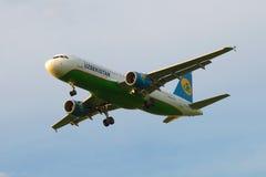 Latać Aerobus A320-214 UK-32020 firma Uzbekistan Airways w chmurnym niebie Obraz Stock