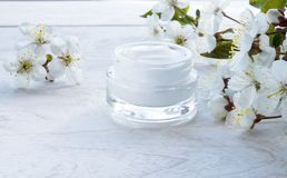 Lata branca, creme cosm?tico e flores da cereja em um fundo branco foto de stock royalty free