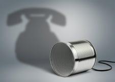 Lata con la sombra del teléfono, concepto creativo de la comunicación fotos de archivo