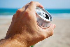 Lata de alumínio da cerveja em uma mão, em uma praia e em um mar masculinos Imagem de Stock