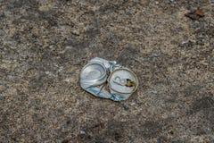 Lata de cerveza machacada en la calle imagenes de archivo