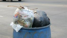 A lata de lixo completa com os grandes sacos de lixo completamente do alimento e do desperdício restantes está na rua video estoque
