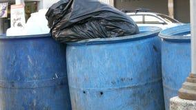 A lata de lixo completa com os grandes sacos de lixo completamente do alimento e do desperdício restantes está na rua vídeos de arquivo