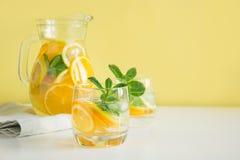 Lata detox lemoniada Woda z cytryną, pomarańcze, lodem i mennicą w glassful, zdjęcia royalty free