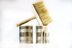 Lata e escovas da pintura em um fundo branco C.A. da pintura e do reparo Fotografia de Stock Royalty Free