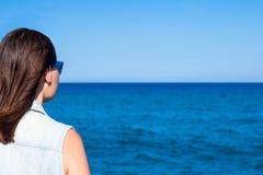 Lata i wakacje pojęcie - tylny widok młoda kobieta nad beac fotografia stock