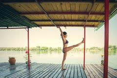 Lata joga kobieta robi joga na rzecznej tratwie Obrazy Royalty Free