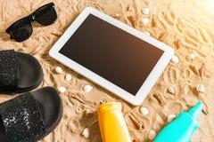 Lata klapy, pastylka, sunglass i seashell na piasku, z miejscem dla twój teksta Odgórny widok Zdjęcie Stock