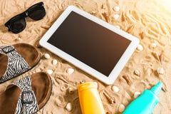 Lata klapy, pastylka, sunglass i seashell na piasku, z miejscem dla twój teksta Odgórny widok Fotografia Stock