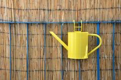 Lata molhando de metal amarelo, cerca de bambu no fundo Fotografia de Stock Royalty Free