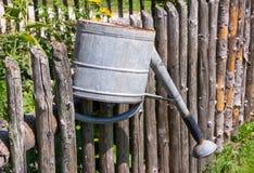 Lata molhando do vintage na cerca de um jardim vegetal Fotografia de Stock Royalty Free