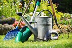 Lata molhando e ferramentas no jardim fotografia de stock royalty free