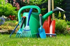 Lata molhando e ferramentas no jardim Fotografia de Stock