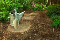 Lata molhando e trowel velhos em um jardim Fotos de Stock Royalty Free
