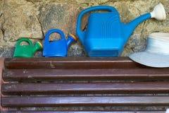 Lata molhando plástica em um banco além da parede de pedra no mandril Imagens de Stock Royalty Free