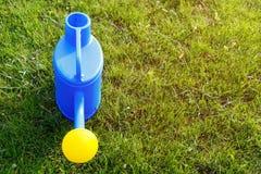 lata molhando pl?stica azul com uma lente amarela em um gramado verde foto de stock royalty free