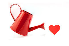 Lata molhando vermelha isolada com coração vermelho no fundo branco imagens de stock royalty free