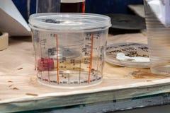 Lata plástica transparente com tiras de medição para pesar e contar a pintura e outros líquidos em uma pintura do carro fotos de stock