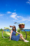 Lata pojęcie - kobiety obsiadanie na trawie z rocznika bicyklem Zdjęcie Stock