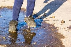 Lata przespacerowania dzieciak w butach w kałuży Fotografia Stock