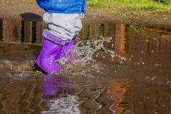 Lata przespacerowania dzieciak w gumowych butach w kałuży Obrazy Royalty Free