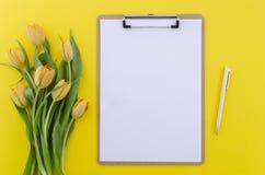 Lata tła odgórny widok żółci tulipany na bielu stole z schowkiem i piórze, kopii przestrzeń dla teksta Sztandaru mockup obrazy stock