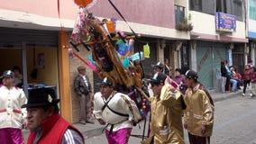 Latacunga, Ecuador - 20180925 - Ashanguero im Weiß befördert 250 Pfund des Festes auf seiner Rückseite in Mutter Negra Parade stock video footage
