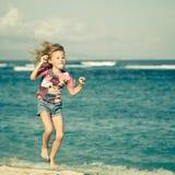 Latająca doskakiwanie plaży dziewczyna przy błękitnym dennym brzeg zdjęcia stock